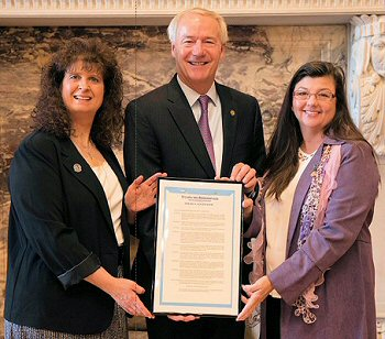 ARSA President Katie Bishop (right) and Vice President Cindy Lewis (left) at the State Capitol with Arkansas Governor Asa Hutchinson (center) and the proclamation for Surgical Technologists Week